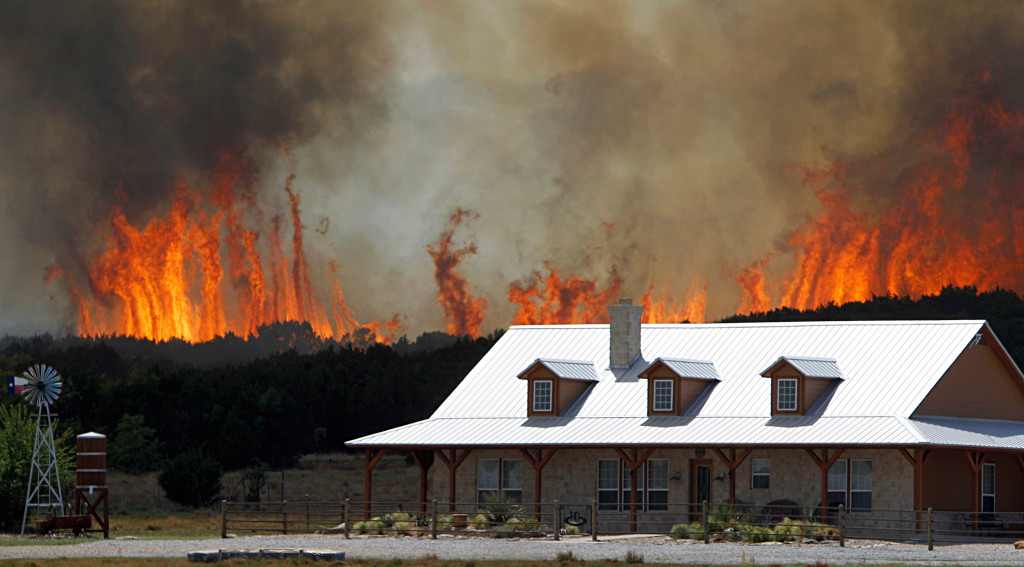 Wildfire threatens a house